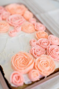 butter cream roses in pink and blush on sheet cake