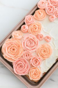 pink buttercream roses on sheet cake