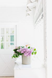 white kitchen and marble with lilacs on counter