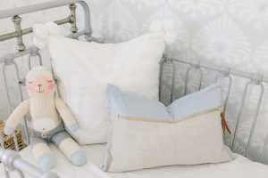grey and blue pillows in metal crib