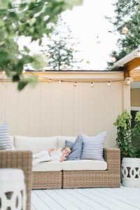 little girl on rattan outdoor couch