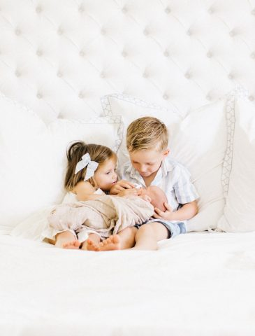 brother and sister cuddling baby brother in bed