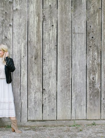 women by barn in white dress and leather jacket