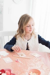 Little girl writing valentines day cards