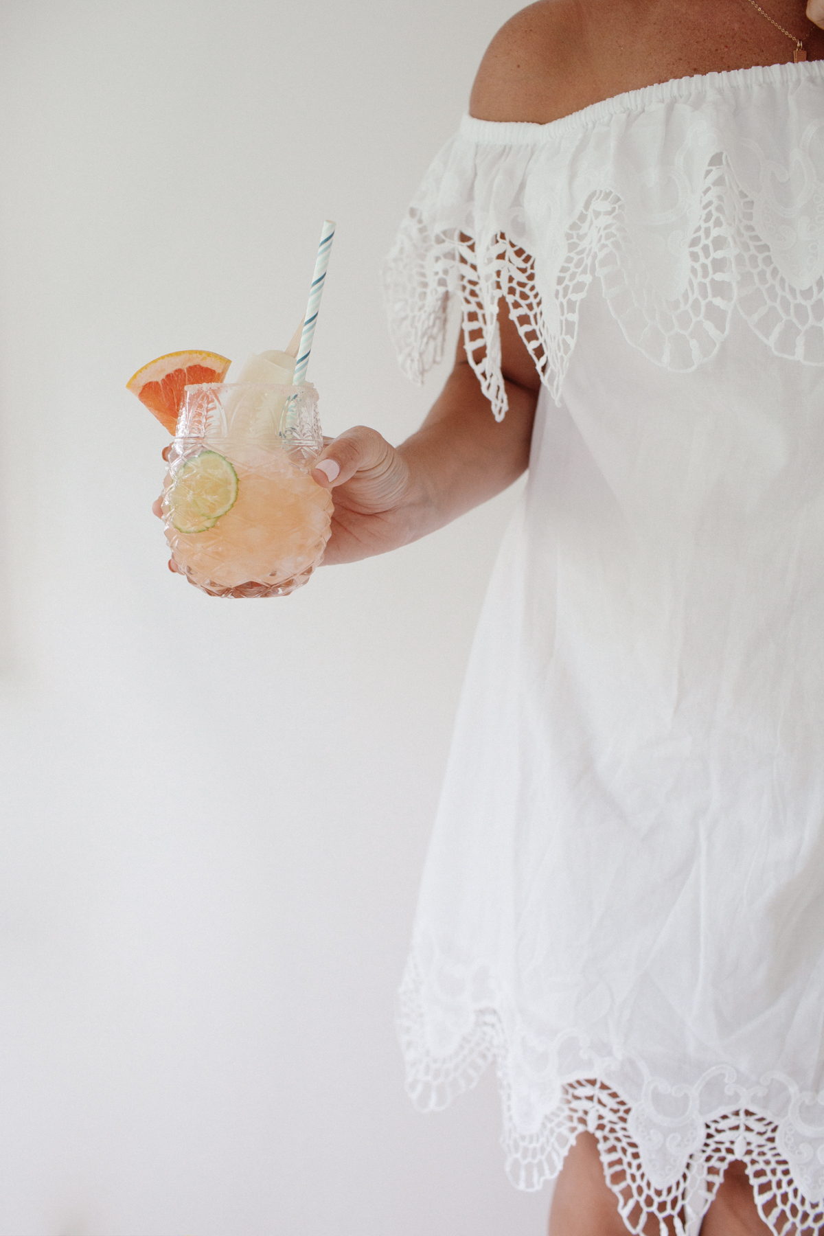 Monika wearing a white dress and holding a glass of grapefruit juice