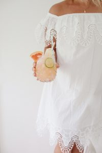 Monika wearing a white dress and holding a glass of grapefruit juice