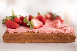 cake topped with icing and strawberries