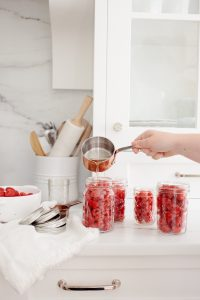 Pouring syrup into jars of raspberries