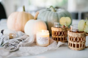 Pumpkins with candle burning and hot apple cider