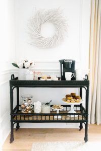black bar cart set up with keurig machine and desserts