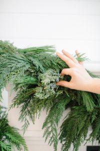 adding juniper into garland on mantel