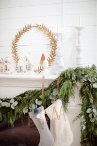 garland on mantel with stockings and glitter homes, candlesticks on the mantel