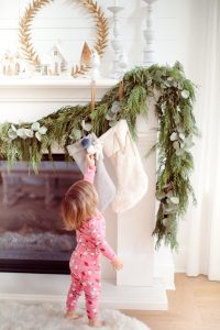 natural garland on fireplace with stocking and toddler