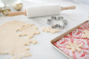 rolling out snowflake cookies