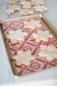 snowflake cookies on sheet pan with festive parchment paper