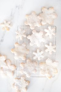 small and large snowflake cookies on marble