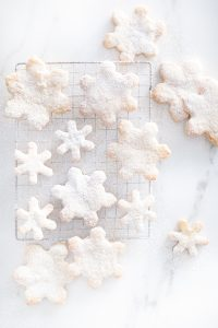 small and large snowflake cookies with icing sugar on marble counter
