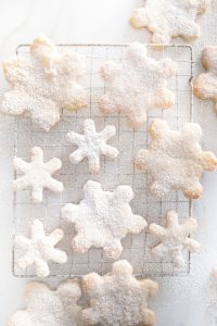 overhead of snowflake cookies dusted with icing sugar on cooling rack