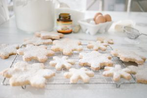 snowflake cookies on cooling rack , ingredients in background