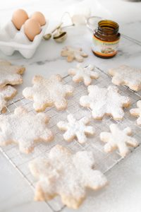 snowflake cookies on cooling rack dusted with icing sugar