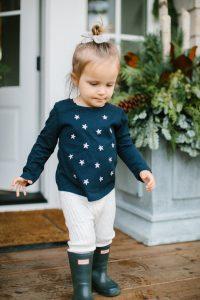 little girl wth stars on shirt walking