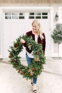 women walking wit large wreath in arms