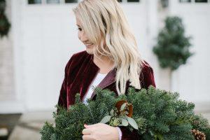 red velvet jacket blond women holding wreath outside
