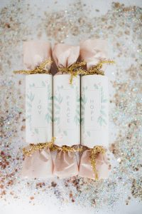 three christmas crackers with glitter around