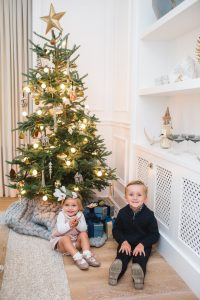 little boy and girl sitting in front of tree