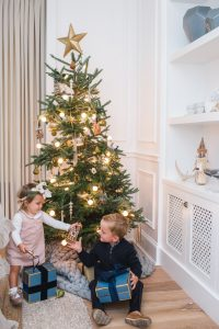 little boy and girl in front of christmas tree
