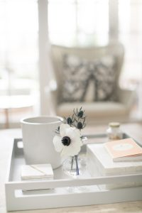 coffe table with candel and bud vase chair in background