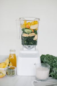 blender with tropical ingredients and kale