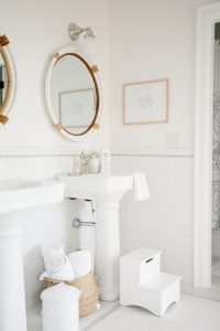 coastal bathroom with step stool by pedestal sink