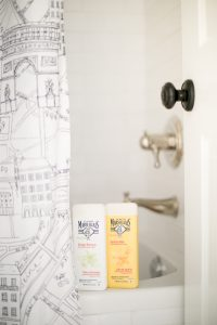 body wash on side of tub with Paris shower curtain
