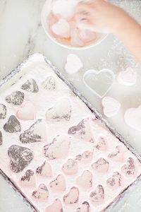 cutting out marshmallows heart shaped and different shades of pink