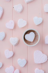 hot chocolate in mug with heart shaped marshmallows on pink board