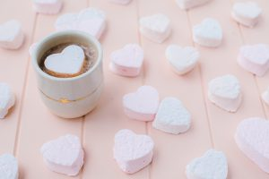 hot chocolate in ceramic mug with heat shaped marshmallow and marshmallows around the mug