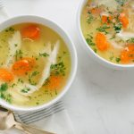bowls of soup with parsley garnish spoon on side