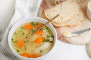 one bowl of chicken noodle soup with bread on cutting board
