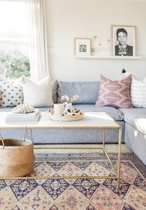 living room light blue couch and woven basket under coffee table