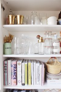 inside kitchen cabinet cookbooks and bar tools