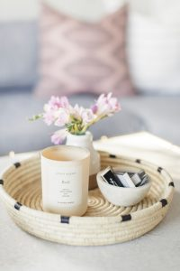 woven basket with candle and small vase of flowers