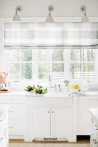 stunning white kitchen with kitchen sink and buffalo check roman blind on window