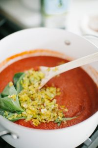 Pot with fresh tomato sauce, basil and leeks