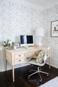 office space with black and white wallpaper and light wood desk