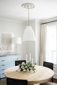 Airy dinning room with light wood table and black chairs