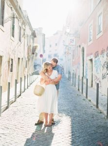 couple kissing on cobblestone streets europe