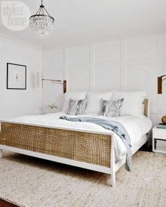 White bedroom with chandelier and large white bed