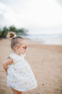 little girl on beach in cute dress and sunglasses