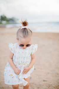 little girl on beach in cute dress hair in a bow